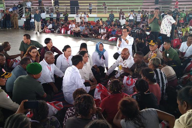 Presiden Joko Widodo sedang duduk bersama dengan para pengungsi korban bencana banjir bandang di GOR Toware, Kabupaten Jayapura (1/4/2019).