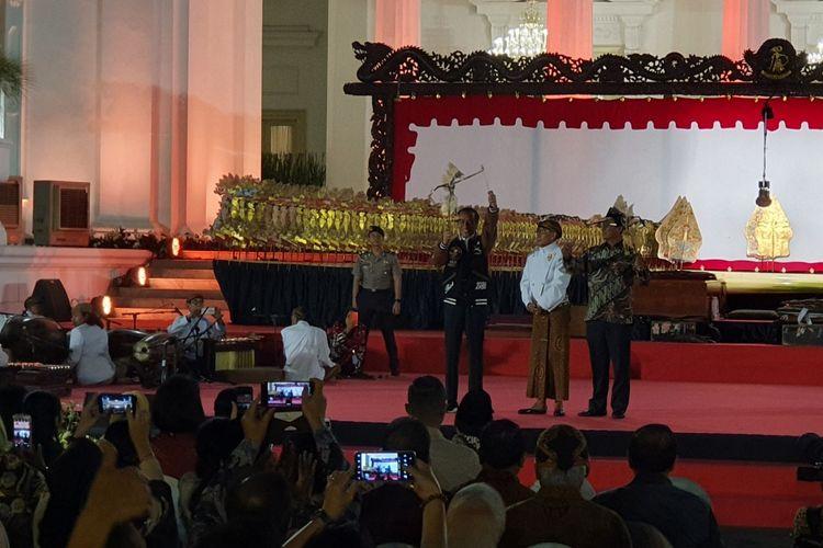 Presiden Jokowi lalu menerima sebuah wayang dari sang dalang Ki Manteb Soedharsono, dalam pagelaran wayang di halaman Istana Merdeka, Jakarta, Jumat (2/8/2019).. Jokowi yang mengenakan jaket bomber berwarna biru sempat memainkan wayang tersebut.