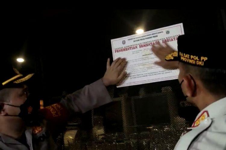 Kapolsek Cilandak, Kompol Agung Permana dan Kepala Satuan Polisi Pamong Praja (Satpol PP) DKI Jakarta, Arifin memasang stiker tanda penutupan Cafe 88, Cilandak Barat, Cilandak, Jakarta Selatan pada Minggu (12/9/2021) dini hari.