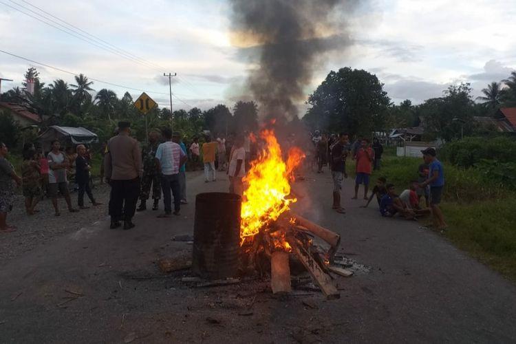 Warga Desa Watludan, Kecamatan Waipia, Kabupaten Maluku Tengah, memblokade Jalan Trans Seram, Kamis (8/7/2021). Pemblokiran jalan dilakukan warga setelah mereka mengambil jenazah pasien positif di RSUD Masohi.