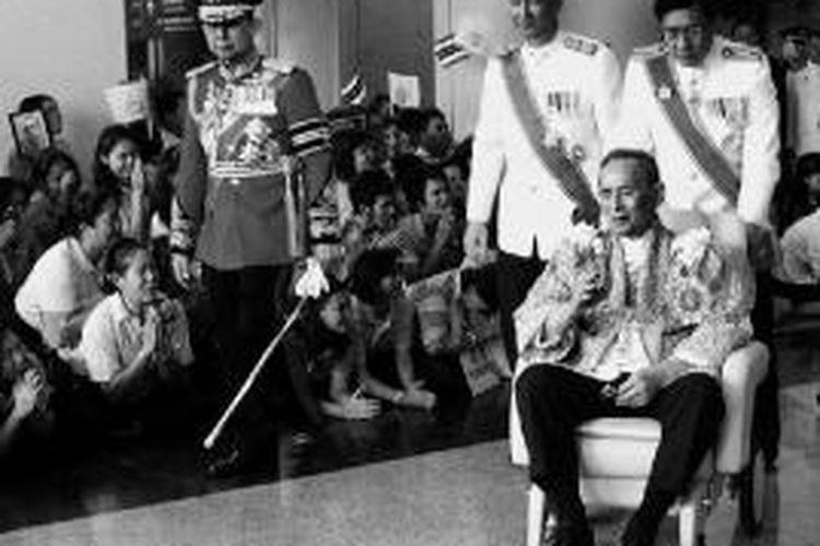Raja Thailand Bhumibol Adulyadej yang duduk di kursi roda membalas sambutan warga yang menunggunya saat kembali ke Rumah Sakit Siriraj dari Istana Agung di Bangkok, Thailand, tempat dia memberikan sambutan dalam perayaan ulang tahunnya yang ke-84, Senin (5/12/2011).