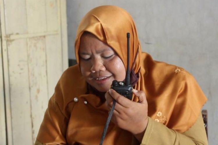 Seorang guru SMPN 3 Satap Punik, Kecamatan Batu Lanteh, Kabupaten Sumbawa, Nusa Tenggara Barat (NTB), mengontak murid-muridnya menggunakan handy talkie.