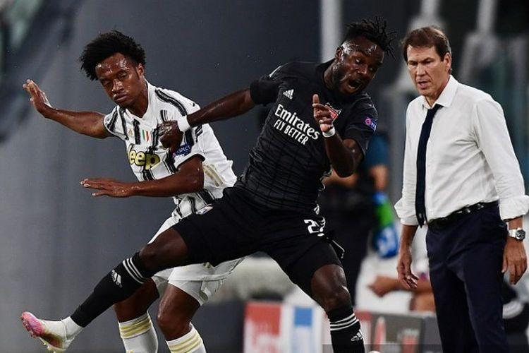 Juan Cuadrado (kiri) berduel dengan Maxwell Gnaly Cornet (kanan) dalam laga leg kedua babak 16 besar Liga Champions Juventus vs Lyon di Stadion Allianz, Sabtu (8/8/2020) dini hari WIB.