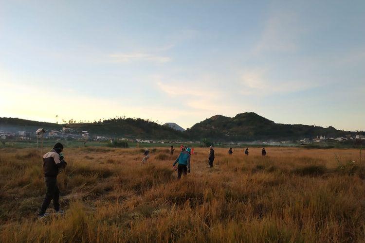 Wisatawan berburu fenomena embun es di lapangan kompleks Candi Arjuna, Dieng, Kabupaten Banjarnegara, Jawa Tengah, Minggu (23/6/2019).