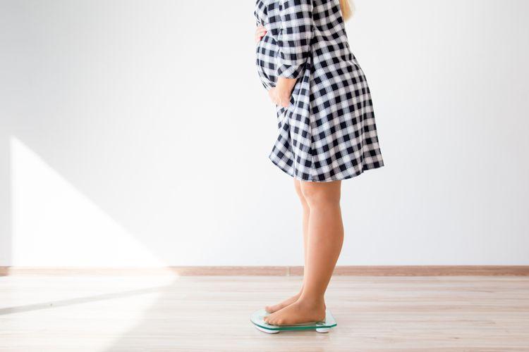 Ilustrasi ibu hamil menimbang berat badan untuk mengontrol bobot tubuh.