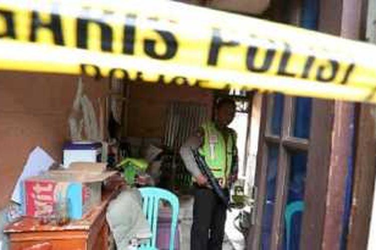 Personel polisi dengan senjata laras panjang berjaga-jaga di sekitar lokasi penggrebekan pengguna narkoba di bantaran sungai Ciiwung, di jalan Slamet Riyadi 4, Kebon Manggis, Matraman, Jakarta Timur, Rabu (20/1).