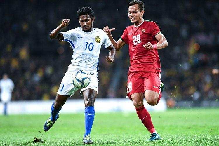 Pemain Malaysia, Kumaahran A/L Sathasivam (kiri), berebut bola dengan pemain Timnas U-22 Indonesia, Rezaldi Hehanusa, dalam pertandingan semifinal SEA Games 2017 di Shah Alam Stadium, Shah Alam, Sabtu (26/8/2017).