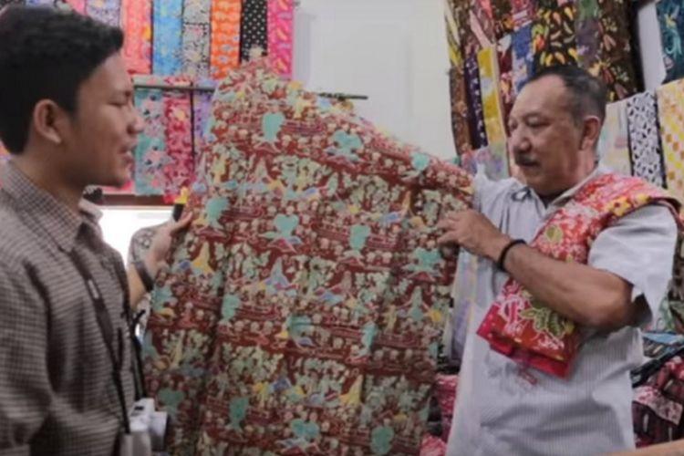 Tri Utomo, pemilik Omah Batik Ngesti Pandowo sedang membedakan batik buatan tangan asli dengan kain tekstil yang hanya dicetak bergambar batik di gerainya, Jumat (16/6/2017).