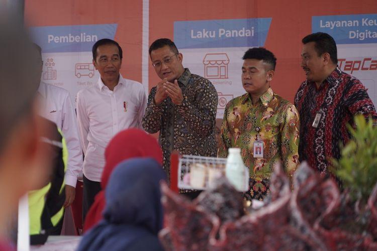 Menteri Sosial Juliari P Batubara menjelaskan kepada Presiden Joko Widodo, tentang berbagai layanan keuangan untuk pelaku ekonomi kecil dan mikro, di sela-sela acara penyaluran bansos PKH Tahap l tahun 2020 di Kota Cimahi,  Jawa Barat, Rabu (29/01/2020).