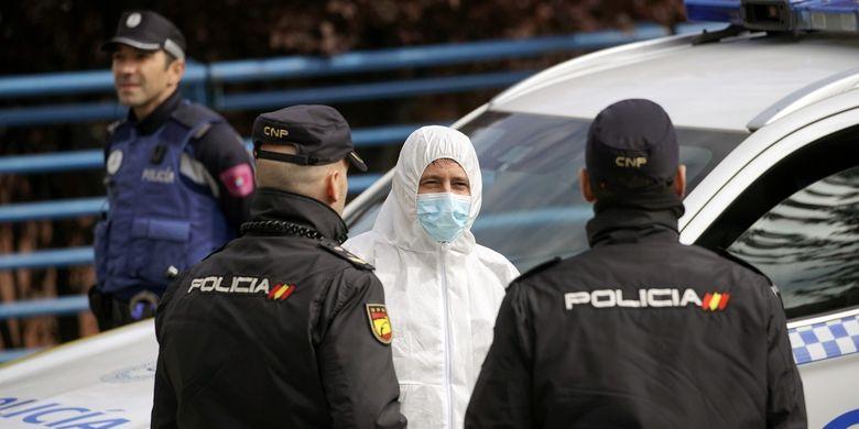Seorang anggota dari militer Spanyol berbicara dengan dua polisi di Madrid, pada 24 Maret 2020, di tengah wabah virus corona.
