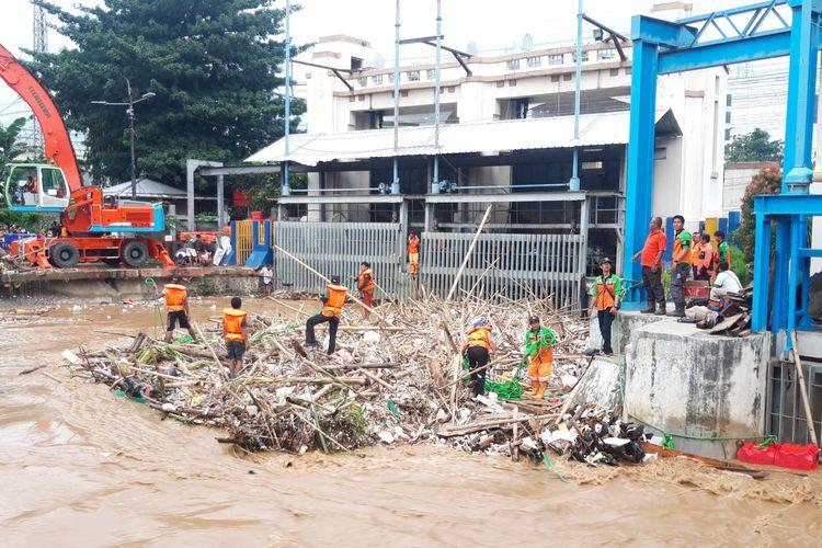 Petugas saat membersihkan sampah di Pintu Air Manggarai, Jumat (26/4/2019)