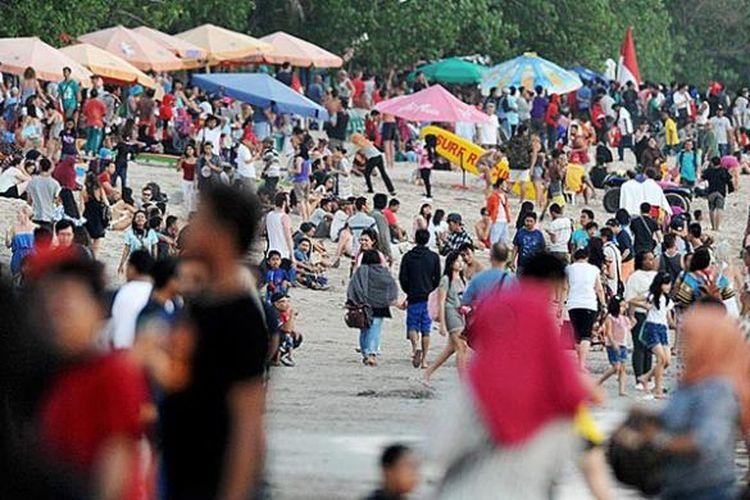 Ribuan wisatawan, baik asing maupun domestik, memadati kawasan Pantai Kuta, Kabupaten Badung, Bali, untuk menunggu matahari terbit, Rabu (17/8/2016). Pantai Kuta merupakan obyek wisata pantai paling terkenal di Bali yang selalu penuh wisatawan pada musim liburan.