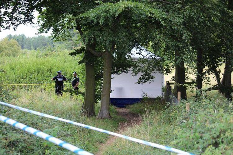 Tenda putih di pasang di lokasi penemuan mayat di kawasan hutan dengan jalan setapak yang biasa digunakan warga, di Desa Harling di timur Norfolk, Inggris.