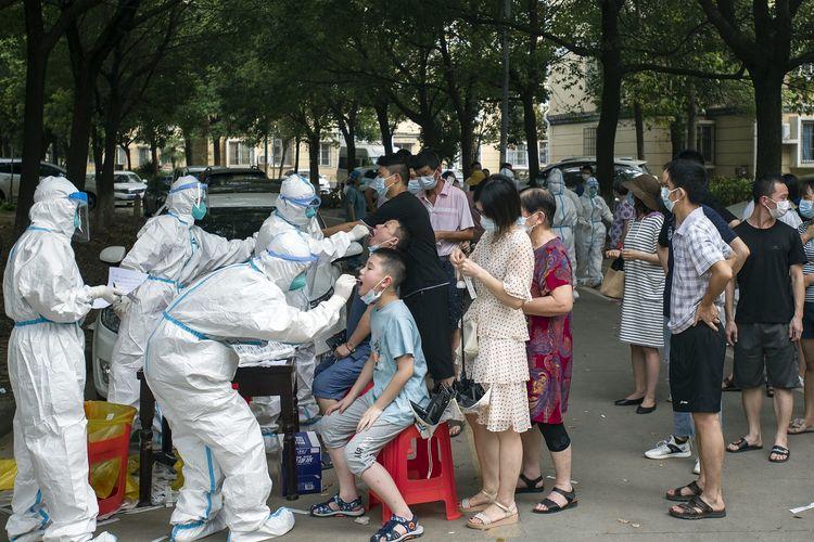 Warga China mengantre untuk tes Covid-19 di Wuhan, provinsi Hubei, Selasa (3/8/2021). Covid-19 varian Delta merebak di China yang membuat pemerintah mengisolasi sejumlah kota, dan menjadi peringatan bagi para pemimpin yang sempat yakin sukses menangani wabah virus corona ini.