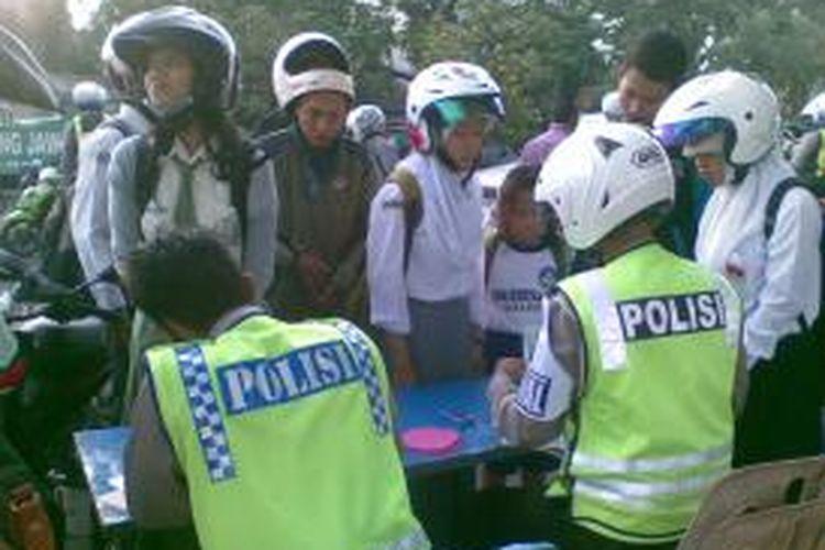 Petugas Satuan Lalu Lintas Polrestabes Surabaya menilang para pelajar yang terjaring razia di Surabaya, Jawa Timur, Rabu (11/9/2013).