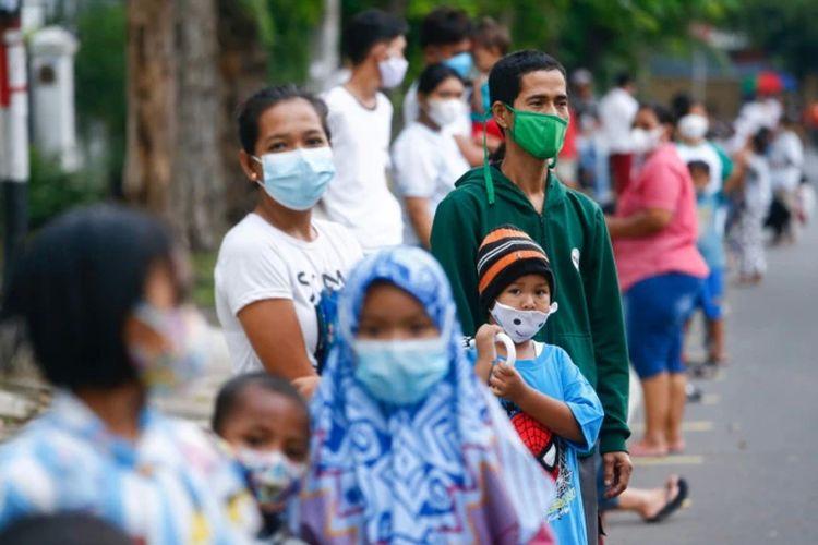 Orang-orang yang mengenakan masker pelindung antre untuk menerima makan gratis berbuka puasa selama bulan suci Ramadhan di tengah pandemi Covid-19 di Jakarta, 15 April 2021.