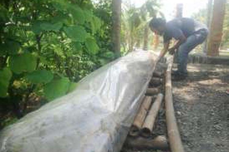 Batu Menhir yang ditemukan ditutup dengan plastik untuk mengurangi kerusakan