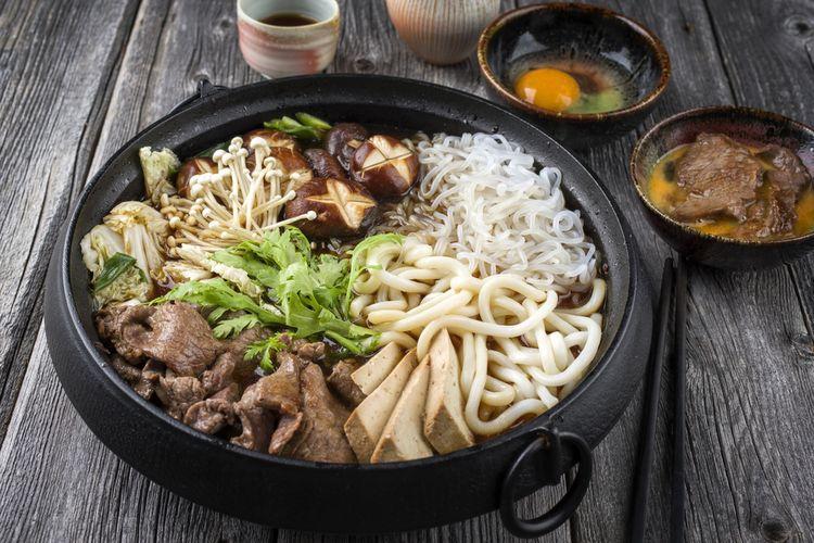 Ilustrasi sukiyaki khas Jepang di wadah besi.