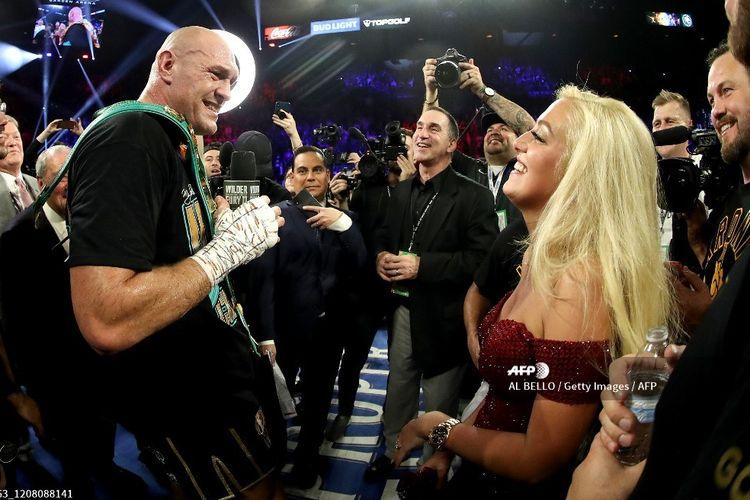 Petinju asal Inggris, Tyson Fury, menyanyikan lagu American Pie di hadapan istrinya, Paris Fury, setelah menang TKO atas Deontay Wilder pada laga perebutan Sabuk Juara WBC Wilder dan gelar Lineal milik Fury di MGM Grand Garden Arena, Las Vegas, Nevada, pada Minggu (23/2/2020) pagi WIB.