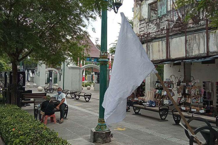 Bendera putih dipasang di sepanjang Jalan Malioboro, DI Yogyakarta, sebagai tanda pedagang kaki lima (PKL) menyerah hadapi pandemi, Jumat (30/7/2021). Para pedagang memasang bendera putih di sepanjang jalan masuk Malioboro hingga di depan kantor Gubernur DI Yogyakarta sebagai simbol ketidakberdayaan dan kesedihan atas kondisi pandemi Covid-19 yang tak kunjung selesai.