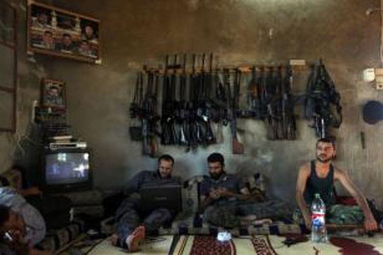 FILE - Tentara Pejuang Pembebasan Suriah duduk di sebuah rumah di pinggiran Aleppo, Suriah, 12 Juni 2012. Foto ini salah satu dari 20 foto karya fotografer AP yang memenangkan Pulitzer Prize 2013 kategori foto Breaking News.