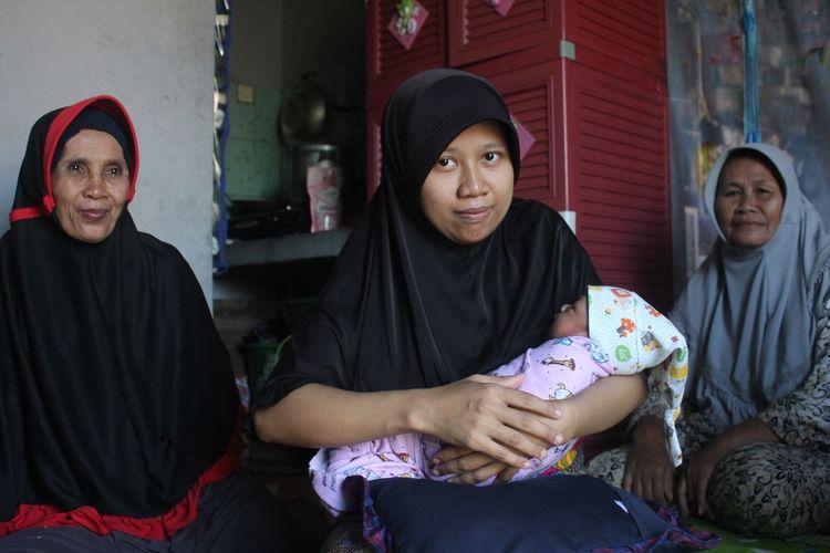 Riska (27), menggendong bayinya, yang baru berumur sepekan di rumahnya di Desa Rahong, Cianjur, Jawa Barat, Jumat (17/01/2020). Riska membayar biaya persalinan anak pertamanya itu menggunakan uang koin pecahan Rp1.000.(KOMPAS.COM/FIRMAN TAUFIQURRAHMAN)