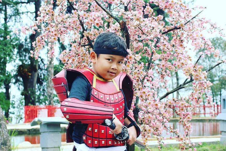Seorang anak berfoto dengan menggunakan seragam samurai berlatarkan pohon sakura ala Jepang di Sakura Hills Tawangmangu, Karanganyar, Jawa Tengah.