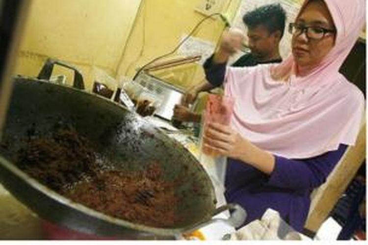 Wildan Kamal dan Istrinya Lutfia Putri Rahmadani, mengemas rendang untuk produksi Naniko Rendang
