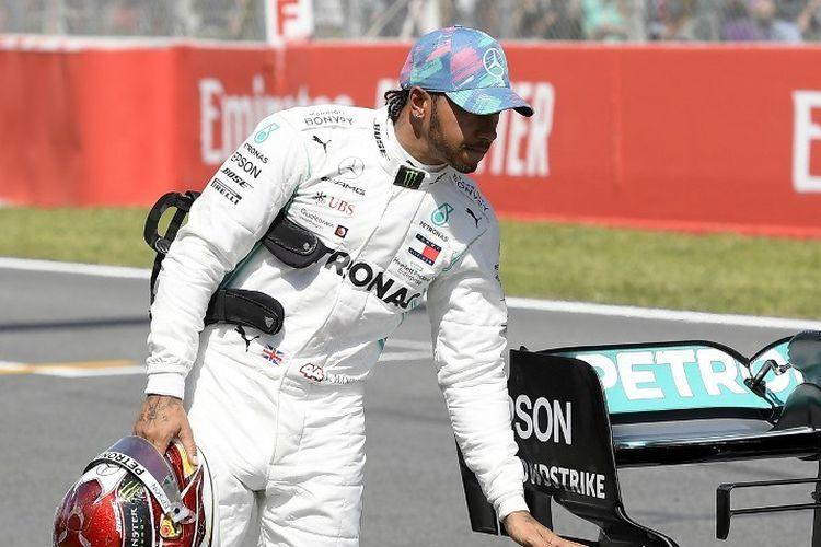 Pebalap Mercedes, Lewis Hamilton, memeriksa ban mobilnya pada sesi kualifikasi GP Spanyol di Sirkuit Catalunya, 11 Mei 2019.