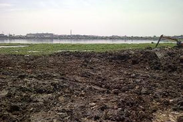 Kendaraan alat berat mengeruk lumpur di Waduk Pluit, Penjaringan, Pluit, Jakarta Utara, Kamis (15/8/2013). Pengerukan tersebut dilakukan untuk mengembalikan fungsi waduk yang mengalami pendangkalan akibat pembangunan kawasan pemukiman liar di sekitarnya.