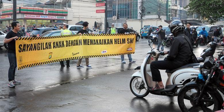 Kampanye pengingat orang tua untuk menyayangi anak dengan menggunakan helm SNI di jalan raya.
