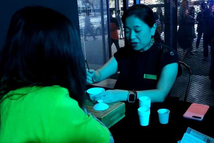 Seorang perempuan sedang mempraktikkan tasseography atau yang juga dikenal dengan sebutan tasseomancy, yakni membaca pola pada ambas daun teh untuk membaca peruntungan di masa depan. Gerai ini menjadi salah satu lokasi yang paling diminati tamu dalam acara Puma SS20 Preview Party, di Subang, Malaysia, Senin malam (2/12/2019).