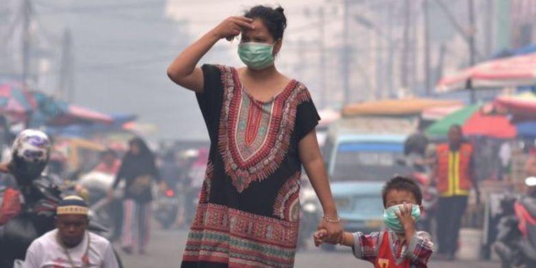 Seorang ibu dan anaknya mengenakan masker medis saat asap kebakaran hutan dan lahan (Karhutla) menyelimuti Kota Pekanbaru, Riau, Selasa (10/9/2019).