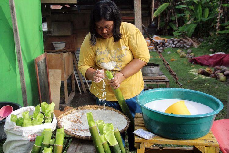 Seorang wanita Jawa Tondano di Yosonegoro mengisi bambu yang dilapisi dengan daun pisang muda dengan beras yang telah dicampur dengan santan, bawang putih dan jahe.