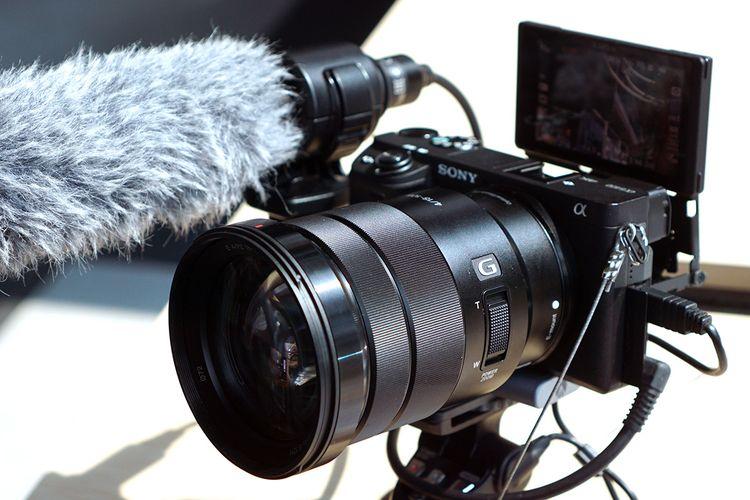 Kamera mirrorless Sony Alpha a6400 dengan aksesori shooting grip GP-VPT1, plate tambahan, mikrofon shotgun. serta lensa SEL 18-105mm F4 dengan zoom elektronik.
