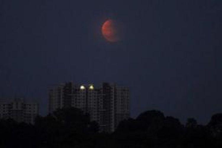 Gerhana bulan terlihat di Bhubaneswar, India, 8 Oktober 2014. Warna merah pada gerhana bulan dipengaruhi oleh pembiasan atmosfer Bumi, disebut dengan 'bulan merah darah'.