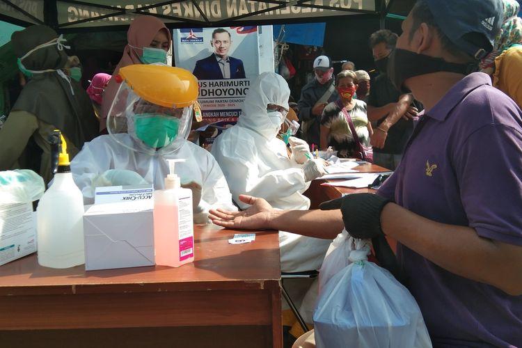 Petugas tengah melakukan tes rapid kepada seorang pedagang Pasar Baru Karawang, Selasa (12/5/2020).