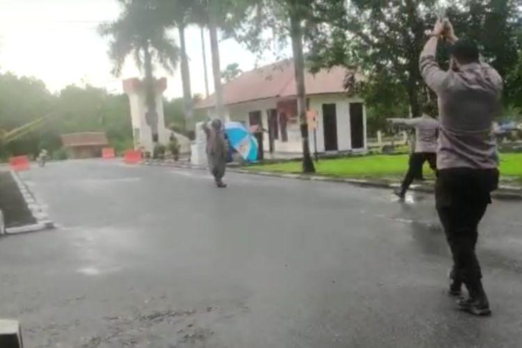 Pria berbaju gamis sambil membawa payung menerobos pintu masuk markas Brimob Polda Sultra, dan dihalau petugas Brimob