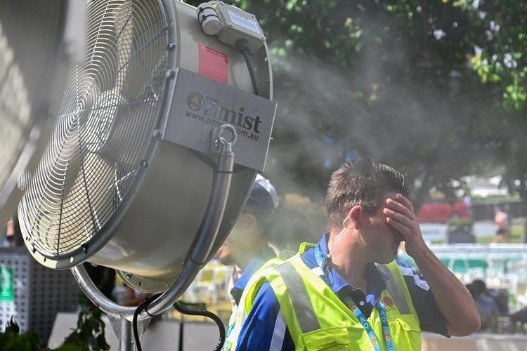 Seorang pria mendinginkan diri di depan kipas angin yang menyemburkan air untuk sedikit mengurangi rasa panas di luar stadion yang menggelar turnamen Australia Terbuka pada Januari lalu. Badan Meteorologi Australia mencatat, bulan lalu menjadi Januari terpanas sejak 1910.