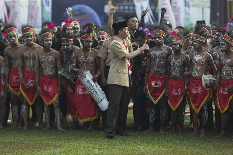 Presiden Joko Widodo (tengah) mengacungkan jempol usai berfoto bersama para anggota pramuka berkostum tradisional Papua dalam acara Raimuna Nasional XI yang bertepatan dengan peringatan ulang tahun Pramuka ke-56 di, Bumi Perkemahan Cibubur, Jakarta, Senin (14/8/2017). Sebanyak 15 ribu Pramuka Penegak dan Pandega dari 34 provinsi dan 514 kota/kabupaten serta pramuka luar negeri mengikuti kegiatan bertajuk Pramuka untuk Masa Depan Indonesia: kreatif, inovatif, berkarakter. ANTARA FOTO/Rosa Panggabean/aww/17.