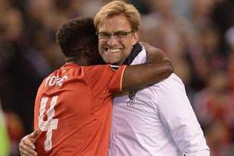 Manajer Liverpool, Juergen Klopp, memeluk salah satu pemainnya, Kolo Toure, setelah timnya menang 3-0 atas Villarreal, dalam laga semifinal kedua Liga Europa di Stadion Anfield, Kamis (5/5/2016) atau Jumat dini hari WIB.