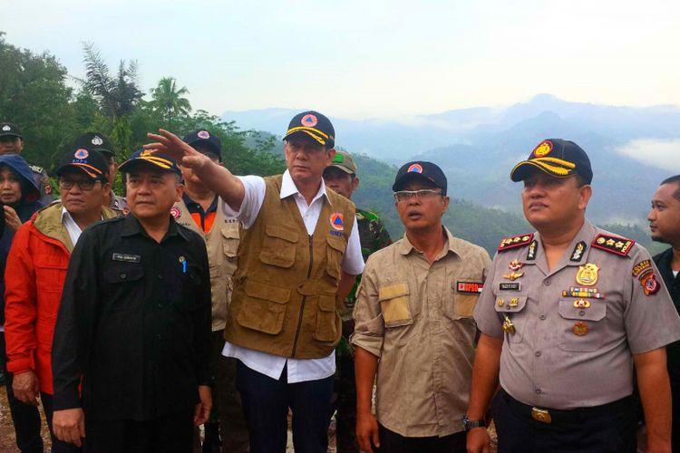 Kepala BNPB Letjen TNI Doni Monardo (kanan ketiga) saat meninjau lokasi lonsor di Dusun Cimapag, Desa Sirnaresmi, Kecamatan Cisolok, Sukabumi, Jawa Barat, Jumat (11/1/2019).