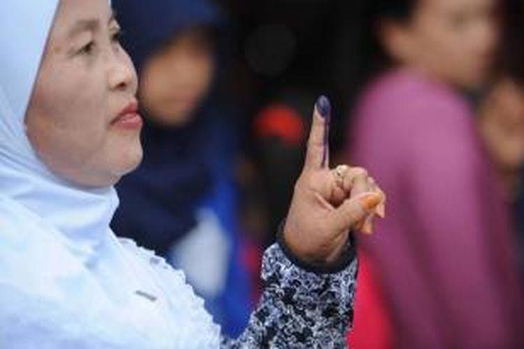 Warga menunjukkan jarinya yang telah dicelup tinta usai menggunakan hak pilihnya dalam Pilpres 2014 di Desa Bojong Koneng, Bogor, Jawa Barat, Rabu (9/7/2014).
