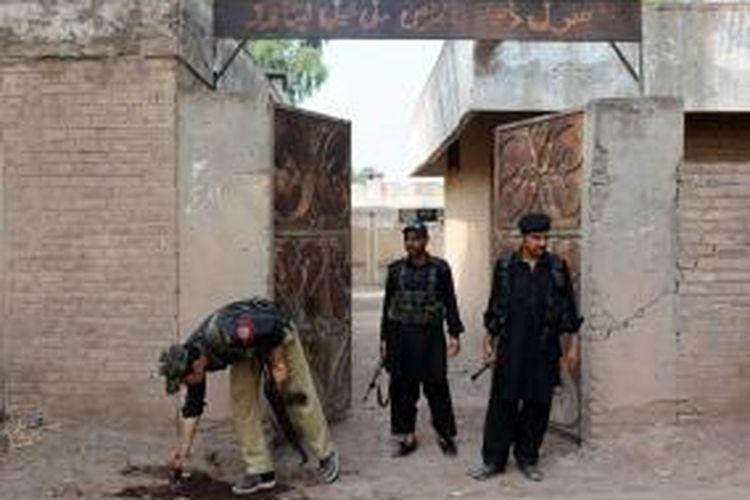 Beberapa anggota polisi Pakistan memeriksa lokasi ledakan bom yang menewaskan seorang polisi yang tengah mengawal para petugas sukarelawan vaksinasi polisi di dekat kota Peshawar, Pakistan.
