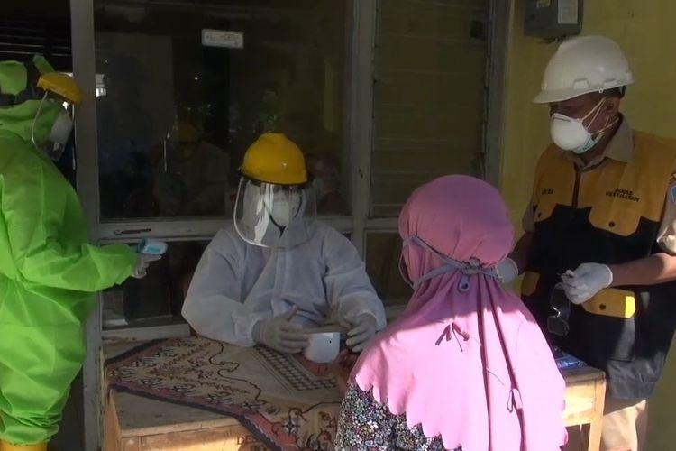 Petugas medis dengan mengenakan APD lengkap melakukan rapid test terhadap satu dari 16 karyawan pabrik kecap yang diisolasi komunal di gedung bekas puskesmas di Desa Penusupan, Pangkah, Kabupaten Tegal, Jawa Tengah, Selasa (14/4/2020)