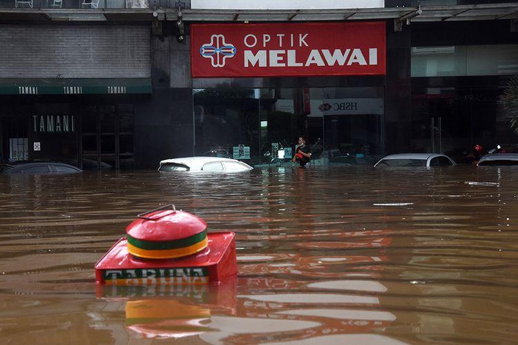 Warga berjalan melewati banjir di kawasan Kemang, Jakarta Selatan, Sabtu (20/2/2021). Banjir yang terjadi akibat curah hujan tinggi serta drainase yang buruk membuat kawasan Kemang banjir setinggi 1,5 meter.