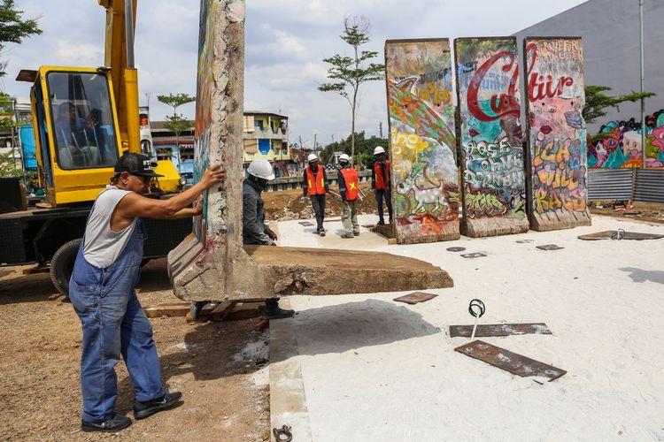 Seniman Teguh Osternik (kiri) melakukan pemasangan batu pecahan tembok berlin di kawasan Ruang Publik Terpadu Ramah Anak (RPTRA) dan Ruang Terbuka Hijau (RTH) Kalijodo, Jakarta Barat, Selasa (26/9/3017). Karya seni instalasi ini bernama Patung Menembus Batas terdiri dari empat pecahan tembok Berlin dan 14 patung baja hasil karya dari seniman Teguh Osternik.