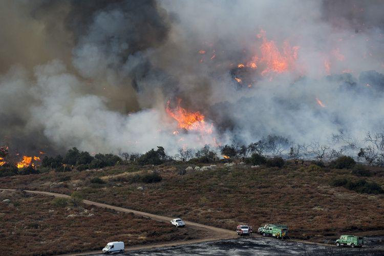 Kebakaran hutan terlihat di sisi bukit Yucaipa, California, pada Sabtu 5 September 2020. Tiga kebakaran hutan yang begitu cepat menyebar membuat warga mengungsi dan lebih dari 200 orang terperangkap di salah satu lokasi perkemahan.