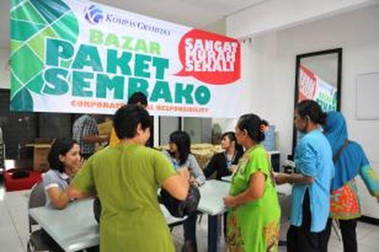 Warga sedang mengantre membeli sembako di bazar murah Kompas Gramedia, Selasa (15/7/2014)