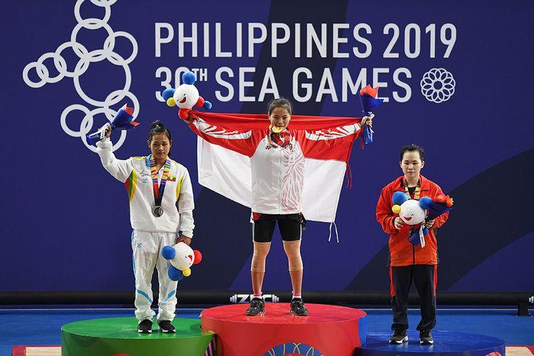 Atlet angkat besi Indonesia Windy Cantika Aisah (tengah) menggigit medali pada upacara penganugerahan medali pertandingan Angkat Besi 49Kg Wanita SEA Games ke-30 di Stadion RSMC Nino Aquino, Manila, Filipina, Senin (2/12/19). Windy Cantika Aisah berhasil meraih medali emas disusul Phyo Pyae Pyae (kiri) dari Myanmar meraih medali perak dan Ngo Thi Quyen (kanan) meraih medali perunggu.